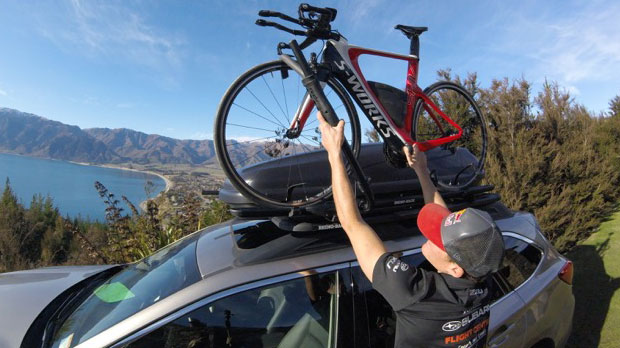 Triathlete Braden Currie putting his bike in the Rhino-Rack bike rack on his Subaru
