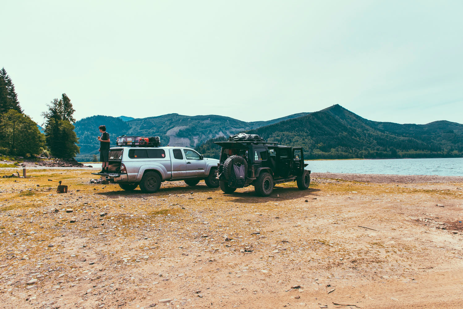 Jeep and Toyota by the water with mountain views