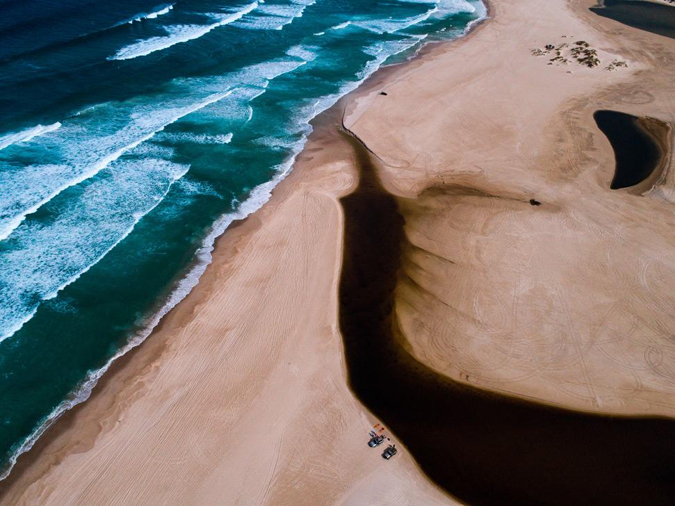 Blacksmiths Beach drone photography: river on the beach